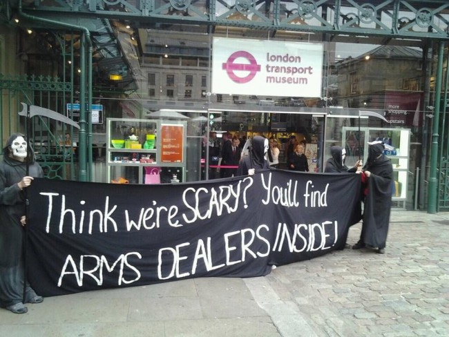 "Three protesters dressed as grim reapers outside the London Transport Museum holding a banner saying ""Think we're scary? You'll find arms dealers inside!"""